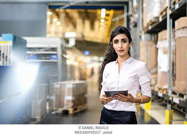 Portrait of woman holding tablet in factory storehouse
