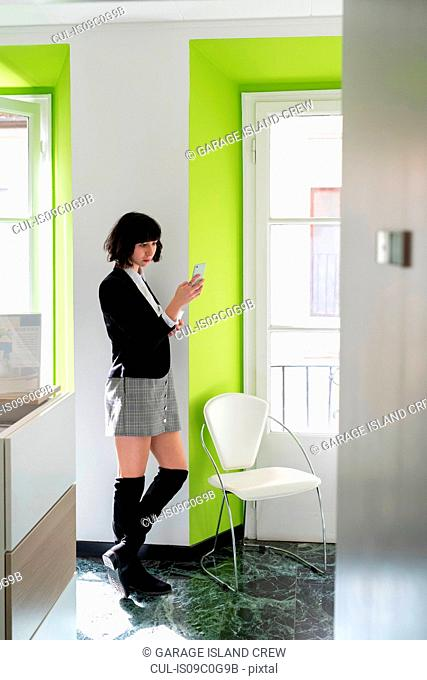 Young female business creative looking at smartphone in office