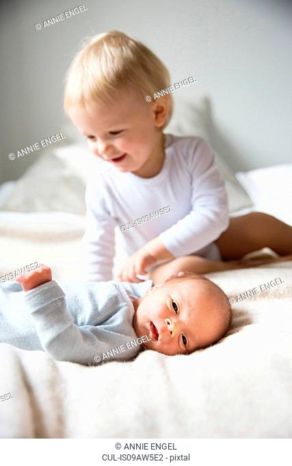 Big brother smiling at baby boy lying on bed