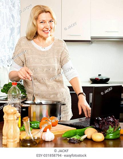Eldery woman using notebook while cooking vegetables at home kitchen