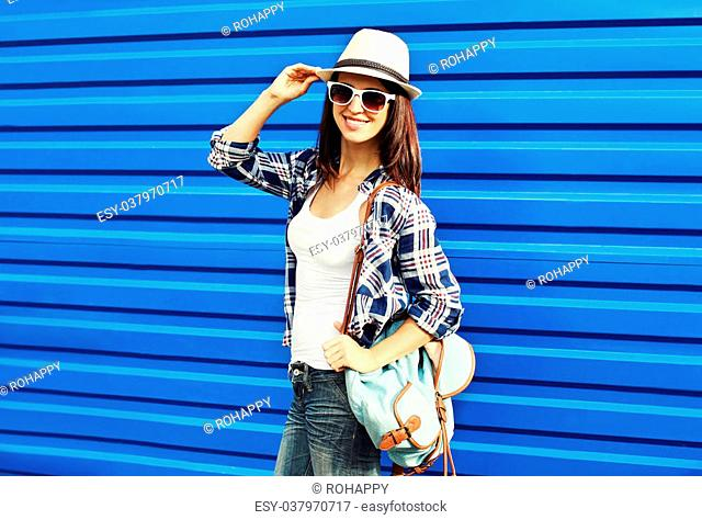 Pretty smiling woman wearing a straw hat, sunglasses and backpack in city