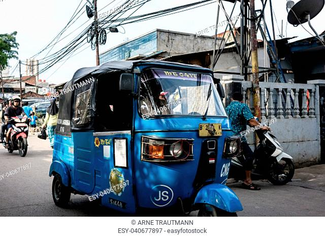 Blue auto rickshaw in motion on a narrow and crowded road in a poor Indonesian village