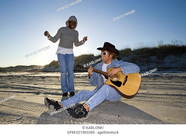 Young interracial couple sitting at beach, man playing guitar, woman dancing