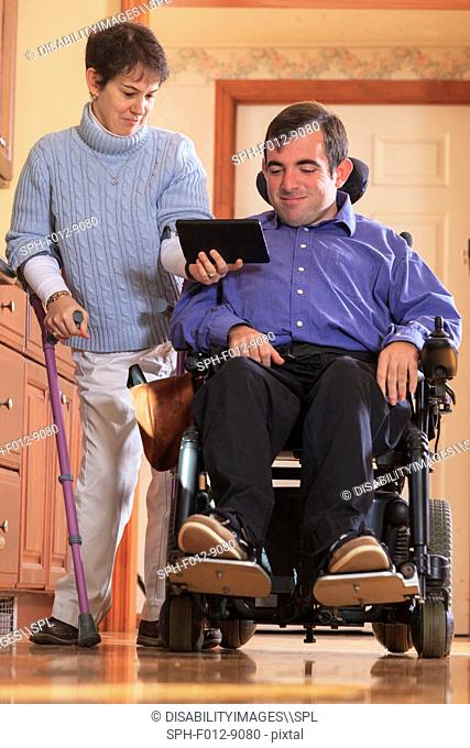 Couple with Cerebral Palsy looking at their tablet