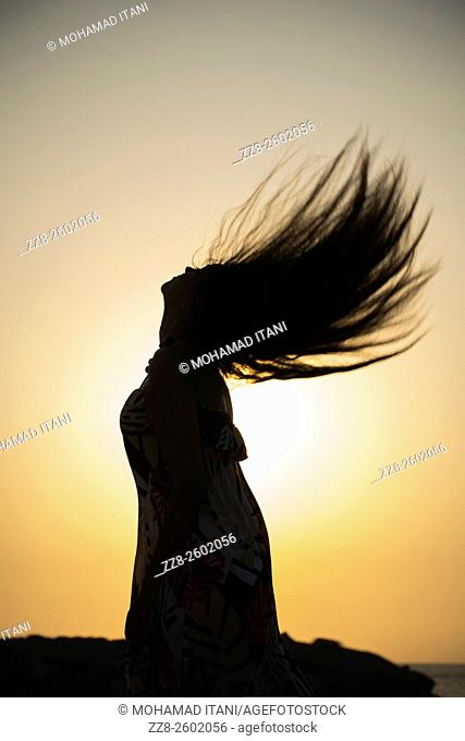 Silhouette of a young woman flicking hair hair against the sunset