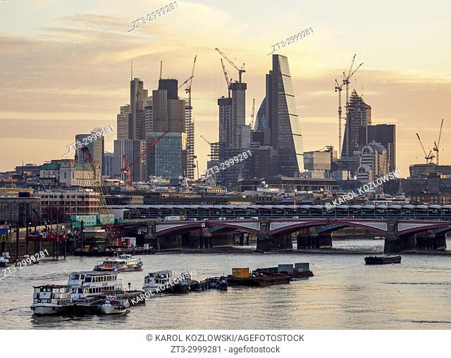 View over River Thames towards City of London at sunrise, London, England, United Kingdom