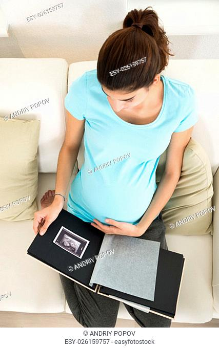 High angle view of pregnant woman looking at ultrasound scan on sofa