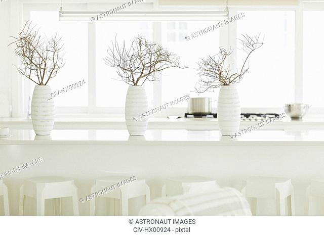 Modern white dining table with white vases and branches