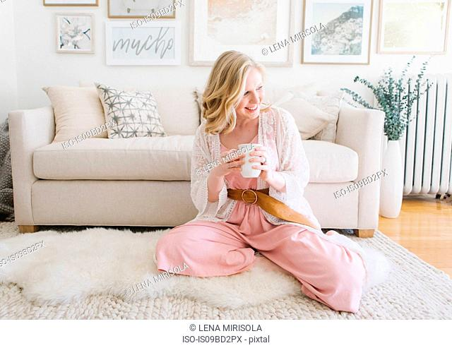 Young woman sitting on living room floor with coffee