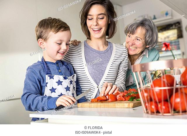 Mother and grandmother helping boy slice tomatoes at kitchen counter