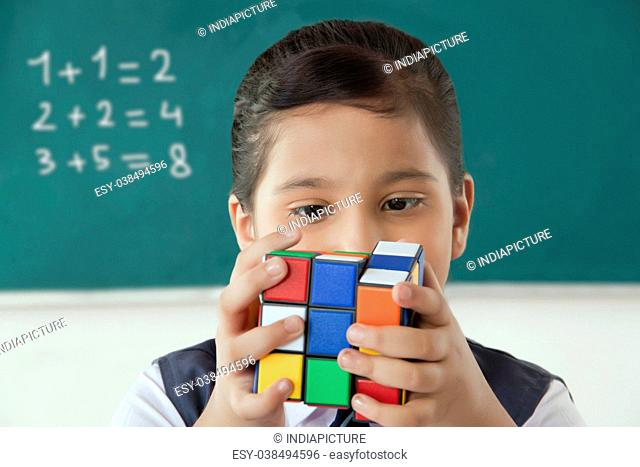 Close-up of girl solving Rubik cube in a classroom