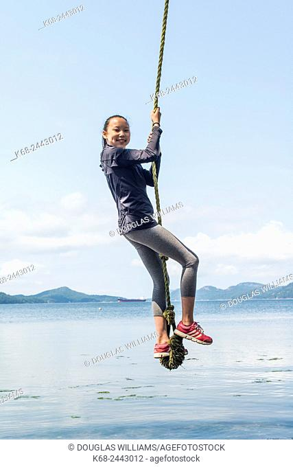 a girl, 12, swings on a rope on Saturna Island, BC, Canada
