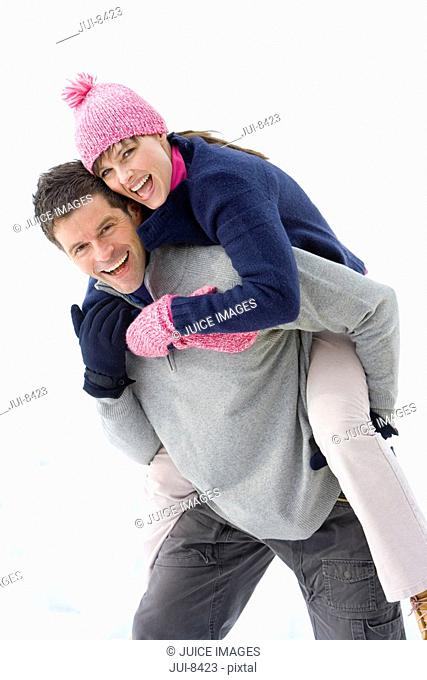 Young couple in snow field, man carrying woman on back, smiling, portrait