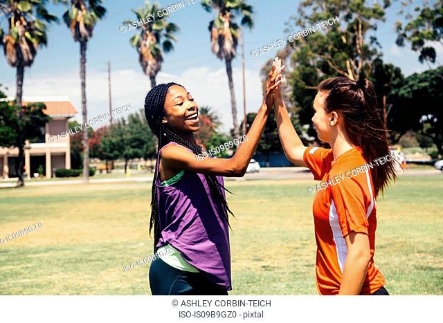 Two teenage soccer schoolgirls high fiving on school sports field
