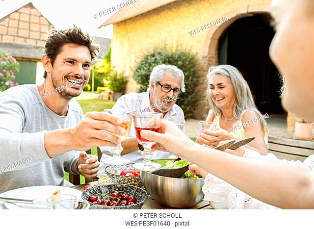 Happy family eating together in the garden, clinking glasses
