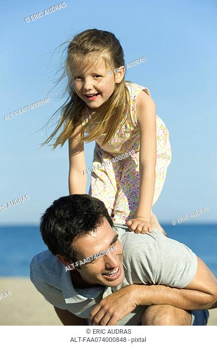 Little girl balancing on her father's back
