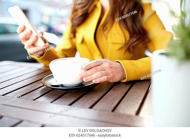 communication, technology, leisure and people concept - close up of young woman or teenage girl texting on smartphone and drinking cocoa at city street cafe...