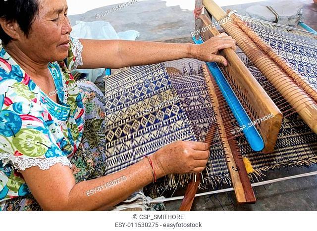 Thai woman weaving straw mat