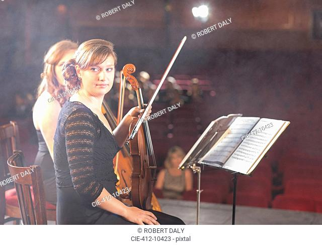 Violinists preparing for performance on theater stage