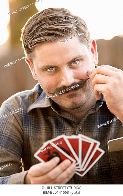 Man twirling his mustache during card game