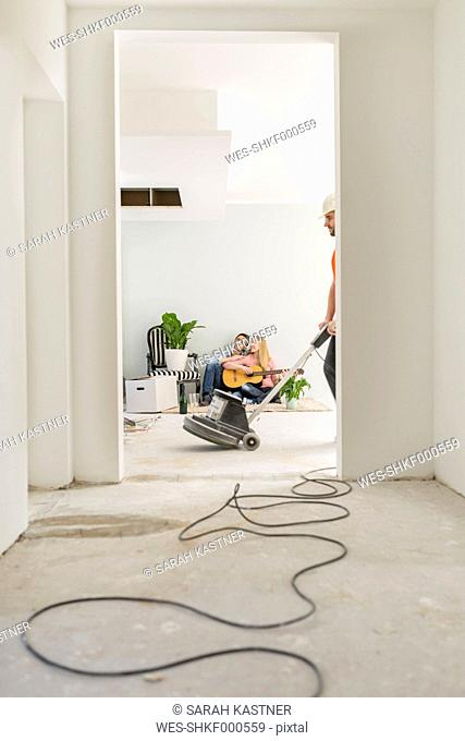 Couple playing guitar at their new home while man working with grinder in the foreground