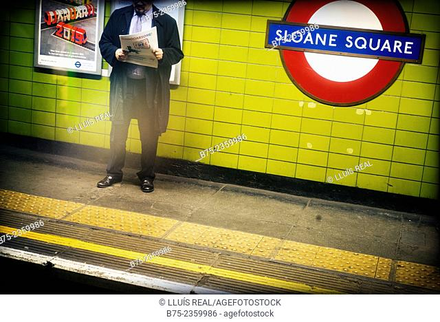 Unrecognizable man reading a newspaper waiting for a train on the platform of a subway station. Sloane square, London, England, UK, Europe