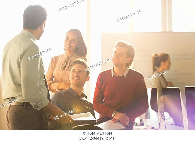 Smiling business people talking in sunny office