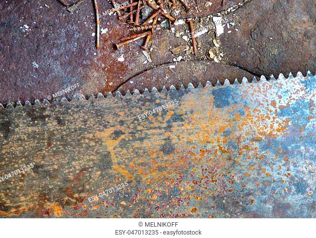 Old rusty texture with different screws and big saw blade. Aged metal - industrial background with place for text. Dirty steel surface in workshop