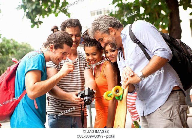 Five adult friends reviewing photos on digital camera, Copacabana town, Rio De Janeiro, Brazil