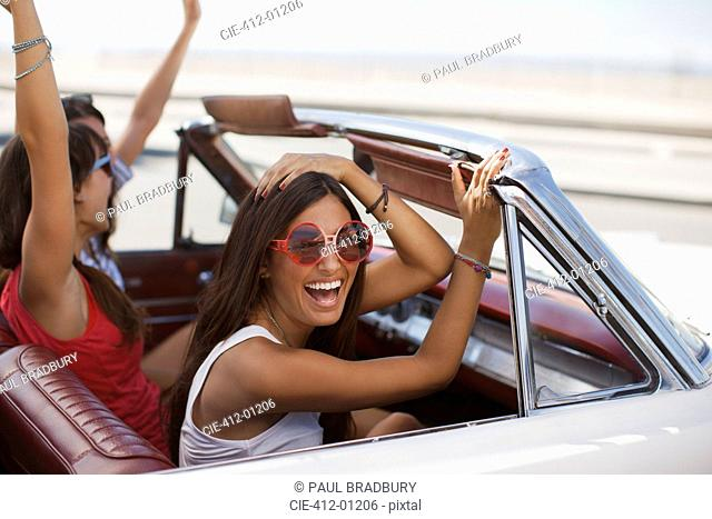 Smiling women driving convertible