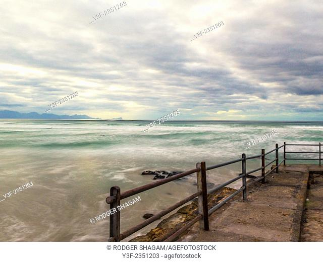 Out-going tide, early morning. Rusted sea-wall railings at Muizenberg Beach, Cape Town, South Africa