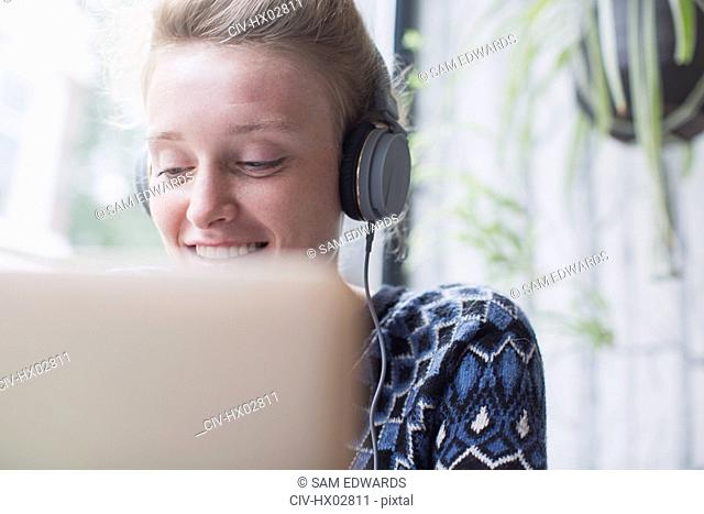 Smiling young woman with headphones using laptop in cafe