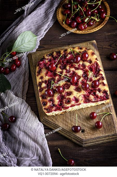 baked cake with cherries on a brown wooden board, next to fresh berries, top view