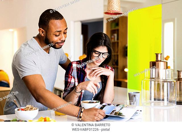 Young couple having breakfast in the kitchen and reading magazine