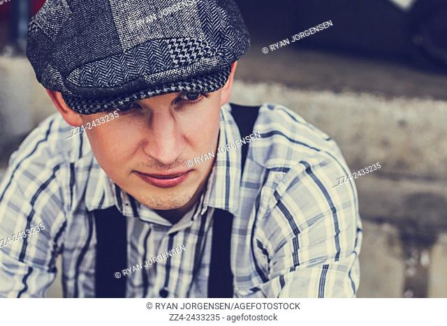 Portrait of a handsome fashionable man musing on an old urban street in classic twenties fashion. All class models