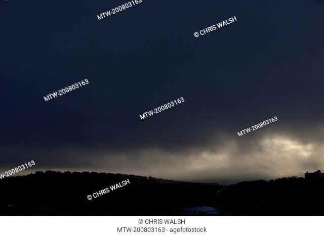 Silhouette row houses dark sky stormy overcast