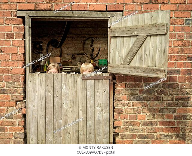 Teenage girl and brother hiding behind barn door