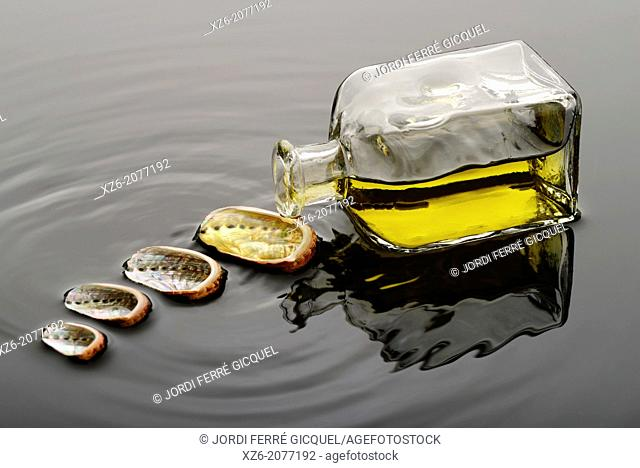Yellow liquid, oil or perfume, spilling from a glass bottle over a seashell on water