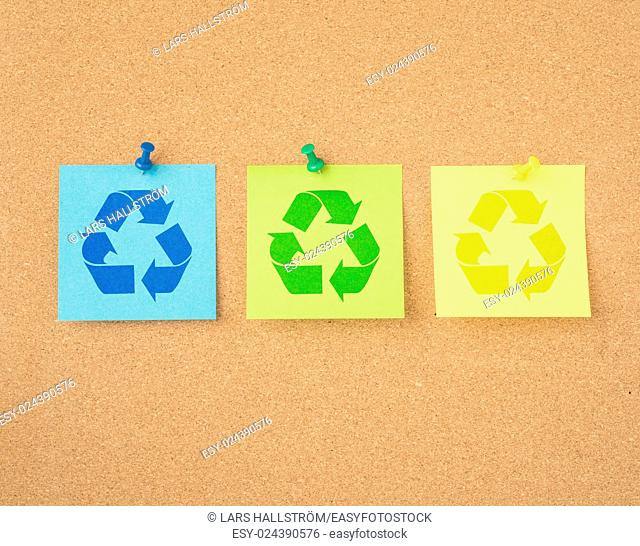 Recycle symbol on paper pinned to message board. Reminder of recycling and green lifestyle
