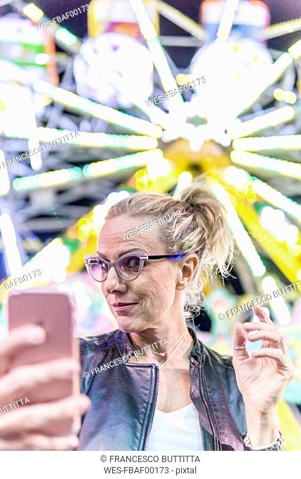 Portrait of mature woman taking selfie in front of big wheel at fair