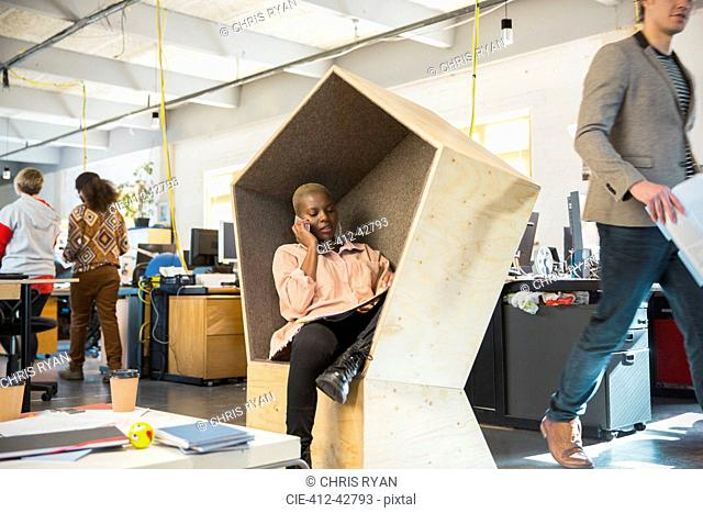 Creative businesswoman talking on smart phone in office cubby