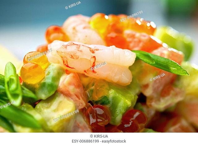 Salad of shrimps, avocado and herbs served with soft caviar. Macro, small depth of field. Blurry background