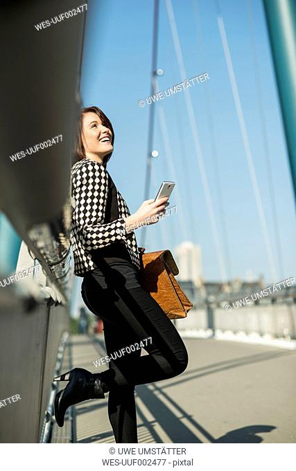 Germany, Frankfurt, young woman on bridge using cell phone