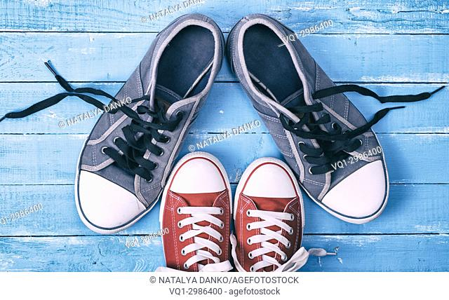 Two pairs of textile sneakers with loose laces stand opposite each other, top view