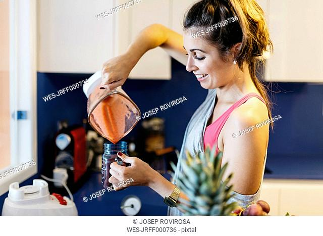 Smiling young woman in kitchen pouring smoothie into mug