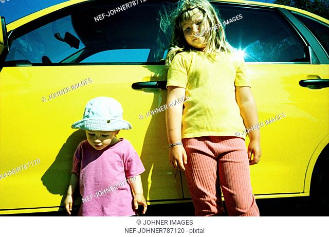 A girl and a boy by a yellow car
