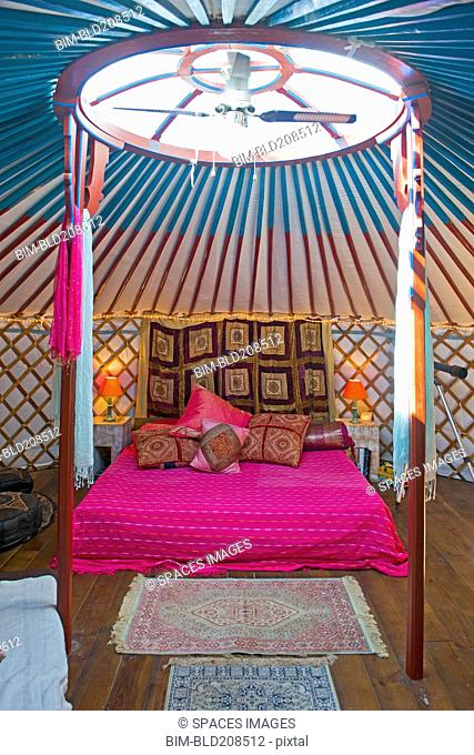 King size bed in a Mongolian yurt with skylight and fan
