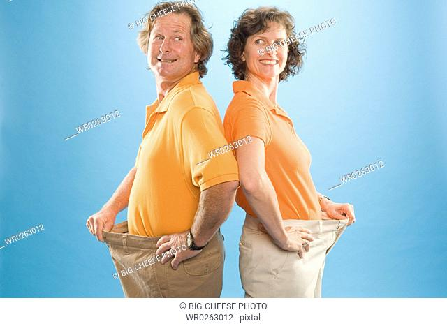 Man and a woman wearing loose pants to show their weight loss