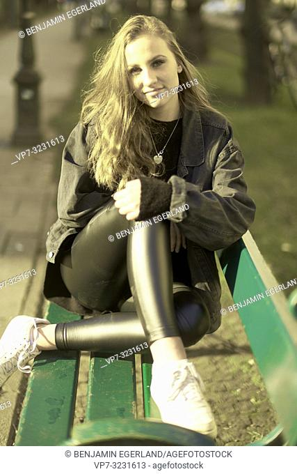 young relaxed teenager woman sitting on bench outdoors in city Munich, Germany