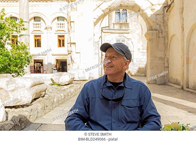 Smiling older Caucasian man sitting in garden